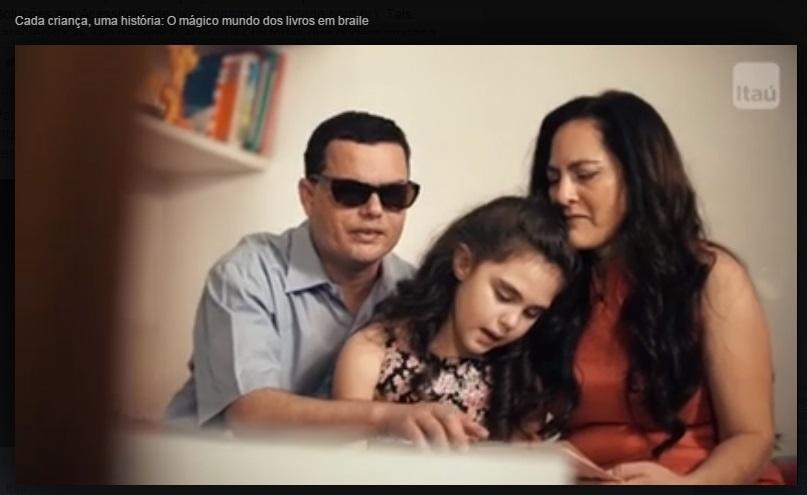 Edson com sua família lendo um livro acessível Braille
