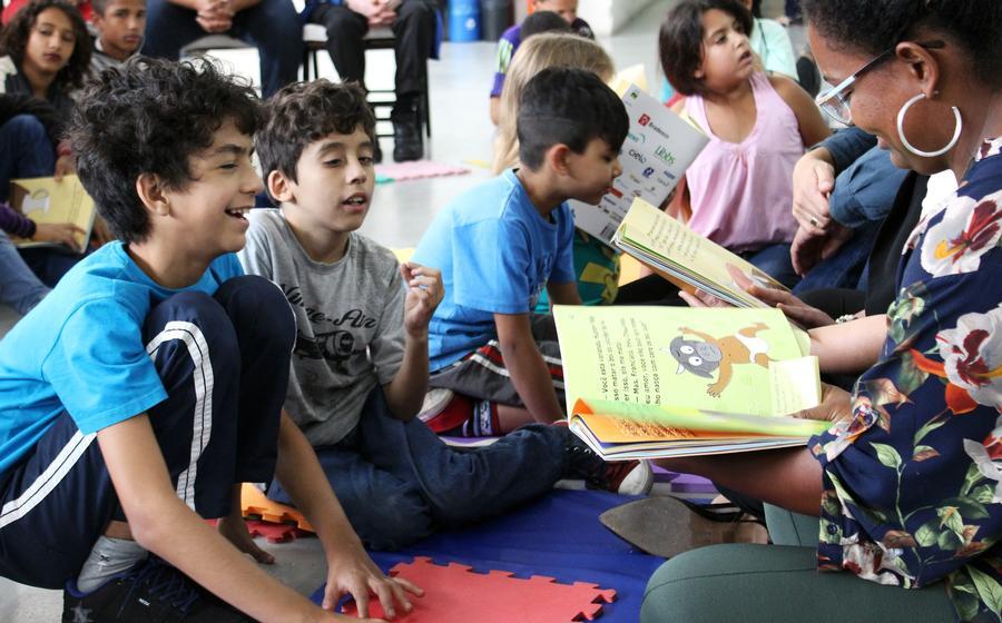 Perla da rede de leitura inclusiva com um livro infantil da Coleção Regionais, está sentada em frente a duas crianças contando uma história. Ao fundo e ao redor existem diversas crianças sentadas também, escutando as histórias contadas.