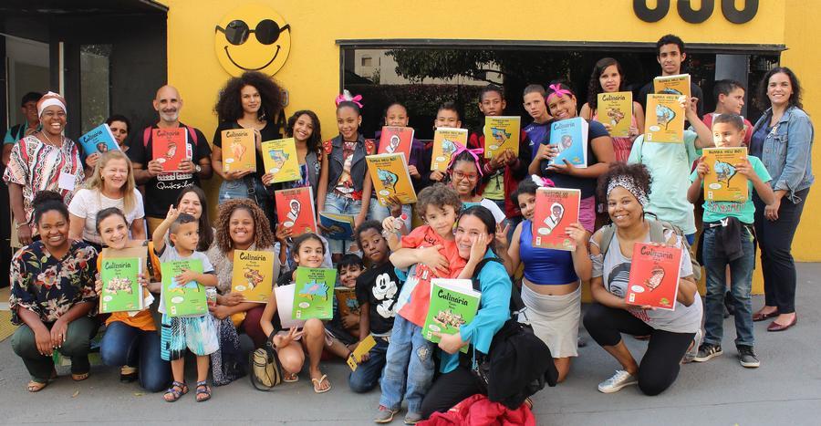 Integrantes da rede de leitura inclusiva: Ana Paula, Perla e Angelita em frente a Fundação Dorina juntamente com vários adultos e crianças que seguram livros da coleção regionais