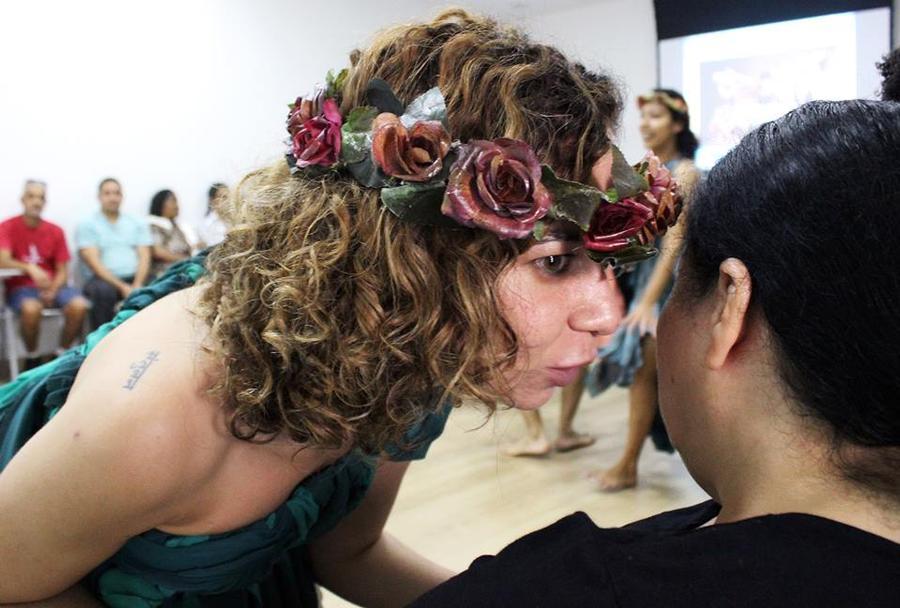 Descrição da imagem: foto de uma das personagens falando ao pé do ouvido de uma mulher da plateia. Ela está de perfil, usa uma coroa de flores e túnica verde, com um dos ombros à mostra.