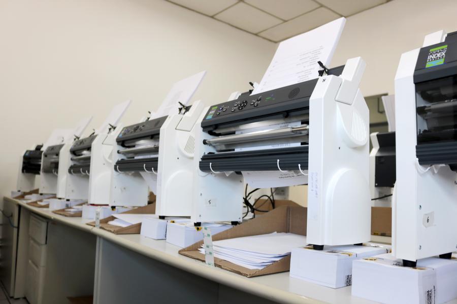 Foto de 6 impressoras digitais braille. Elas estão dispostas lado a lado em cima de uma grande mesa branca. Cada impressora tem um painel preto com botões e nas laterais duas bases brancas grandes que as deixam suspensas sobre uma caixa de papelão em que os papeis impressos caem.