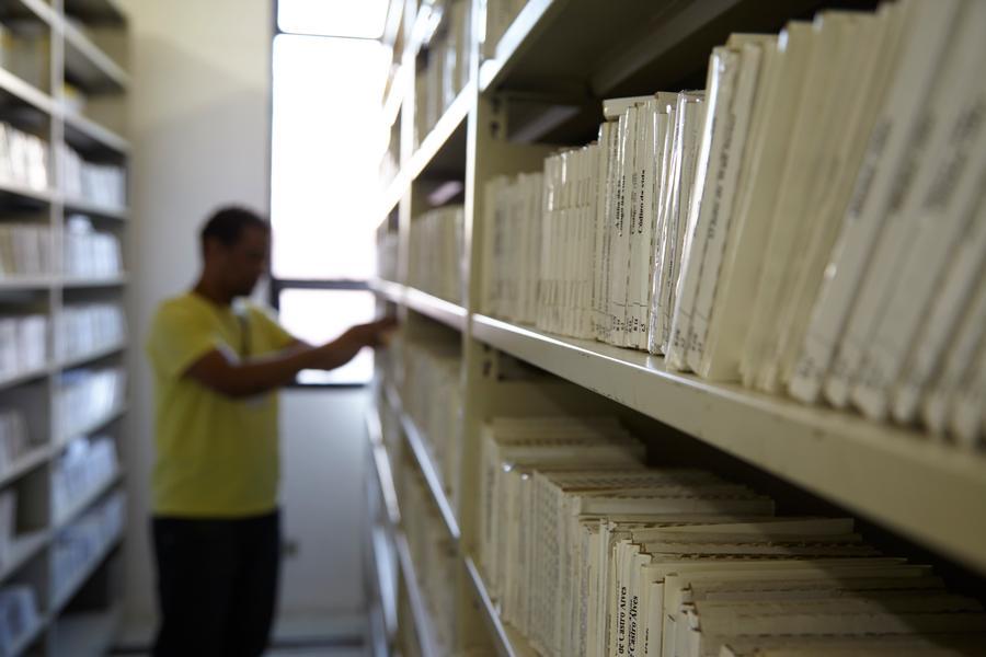 Ezequiel funcionário que atende na biblioteca circulante de livros falados da Fundação Dorina no acervo escolhendo algum título.